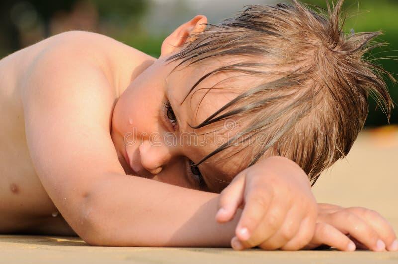 Boy sunbathing. Wet young boy lying on beach an sunbathing royalty free stock image