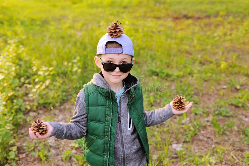Boy in sunglasses with bumps in his hands and on his head against the forest. Child boy in sunglasses with bumps in his hands and on his head against the forest royalty free stock images