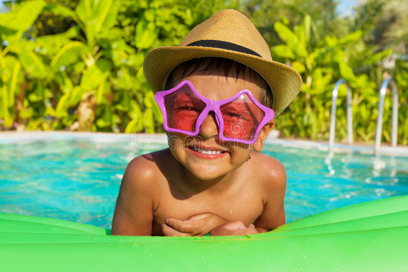 Boy in sunglasses on green airbed, swimming pool. Boy in star-shaped sunglasses on green airbed in the swimming pool outside in summer stock photography