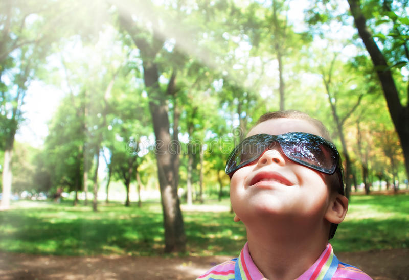 Boy in sunglasses. Looking at the sun stock image