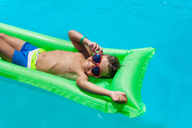 Boy with sunglasses relaxing in swimming pool. Boy with sunglasses relaxing on green inflatable mattress in swimming pool during summer stock photography