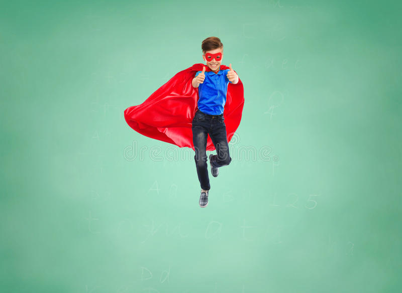 Boy in super hero cape and mask showing thumbs up. Education, gesture, childhood, and people concept - boy in red super hero cape and mask flying in air and stock images