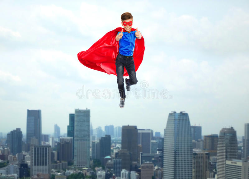 Boy in super hero cape and mask showing thumbs up. Gesture, freedom, childhood, movement and people concept - boy in red super hero cape and mask flying in air royalty free stock photo
