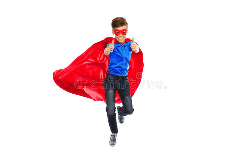 Boy in super hero cape and mask showing thumbs up. Happiness, freedom, childhood, movement and people concept - boy in red super hero cape and mask flying in air royalty free stock photo