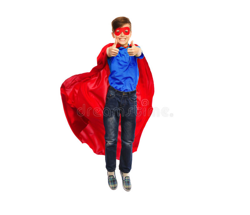 Boy in super hero cape and mask showing thumbs up. Happiness, freedom, childhood, movement and people concept - boy in red super hero cape and mask flying in air royalty free stock images