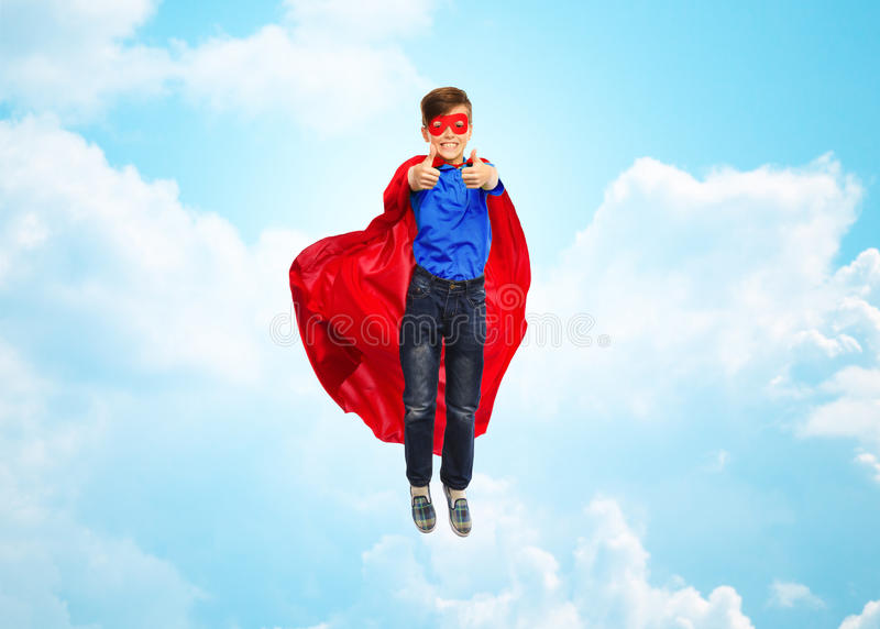 Boy in super hero cape and mask showing thumbs up. Happiness, freedom, childhood, movement and people concept - boy in red super hero cape and mask flying in air stock photography