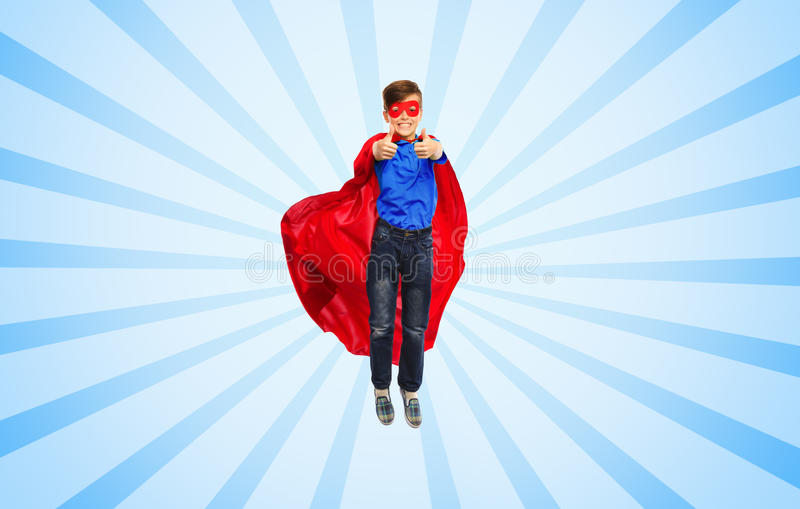 Boy in super hero cape and mask showing thumbs up. Happiness, freedom, childhood, movement and people concept - boy in red super hero cape and mask flying in air stock images