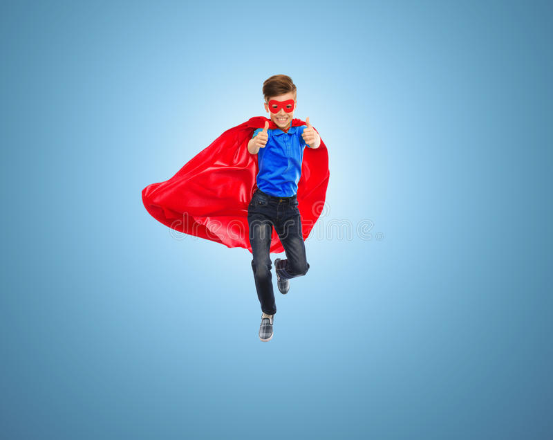 Boy in super hero cape and mask showing thumbs up. Imagination, gesture, childhood, movement and people concept - boy in red super hero cape and mask flying in stock images