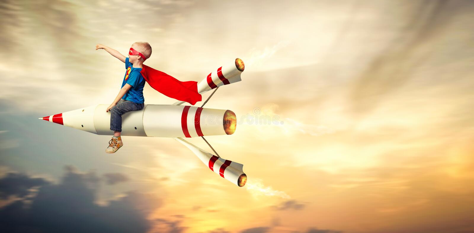 Boy in superhero costume fly on a rocket and show super abilities. stock photos