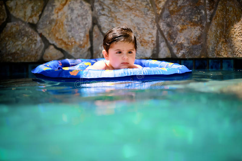 Boy swimming. Little baby boy floating in a swimming pool for the first time stock image