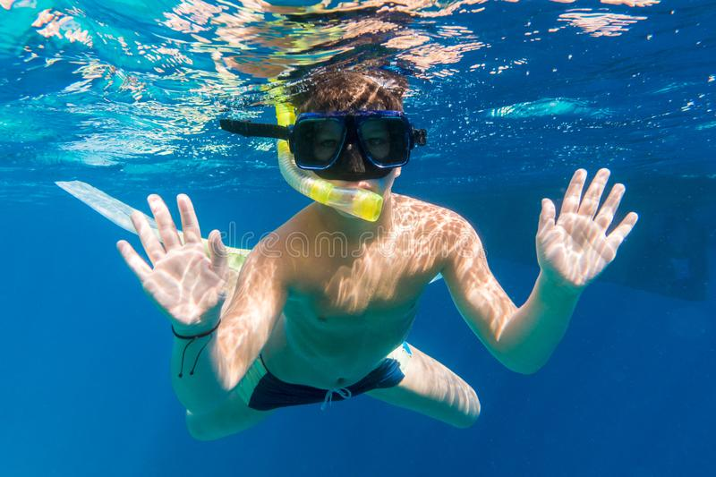 Boy in swimming mask dive in Red sea near yacht. Underwater shoot royalty free stock photo