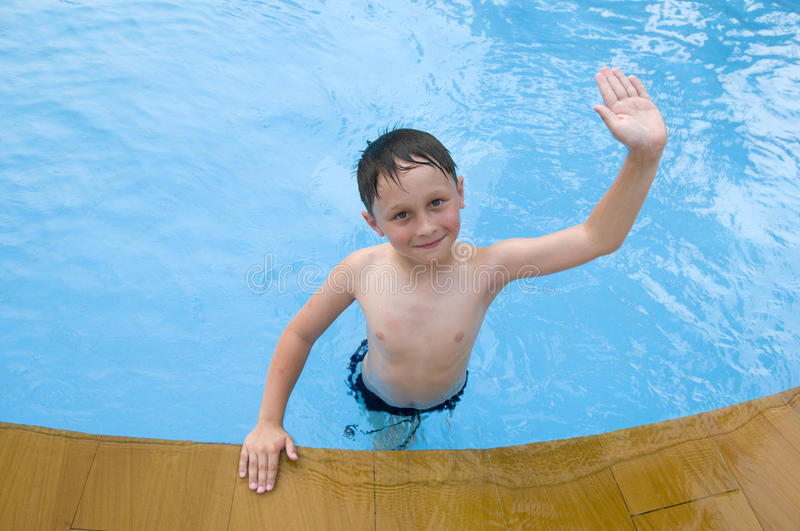 Boy in the swimming-pool. Child waves a hand royalty free stock image