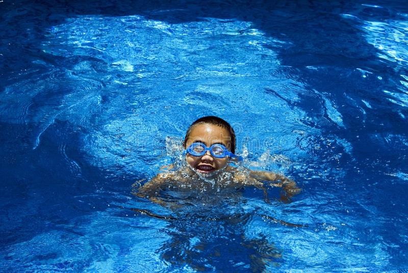Boy in the swimming pool. A view of an asian boy swimming in the pool stock image