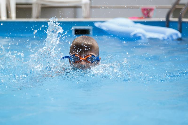 Boy swimming in the pool. Kid, kids, underwater, fun, child, summer, person, vacation, splash, young, smile, blue, dive, swimmer, happy, diving, white, play royalty free stock images