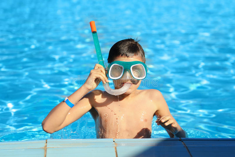 Boy in a swimming pool. With scuba diving mask and tube stock images