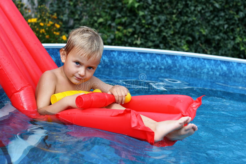 Boy in the swimming pool. With skittles stock image