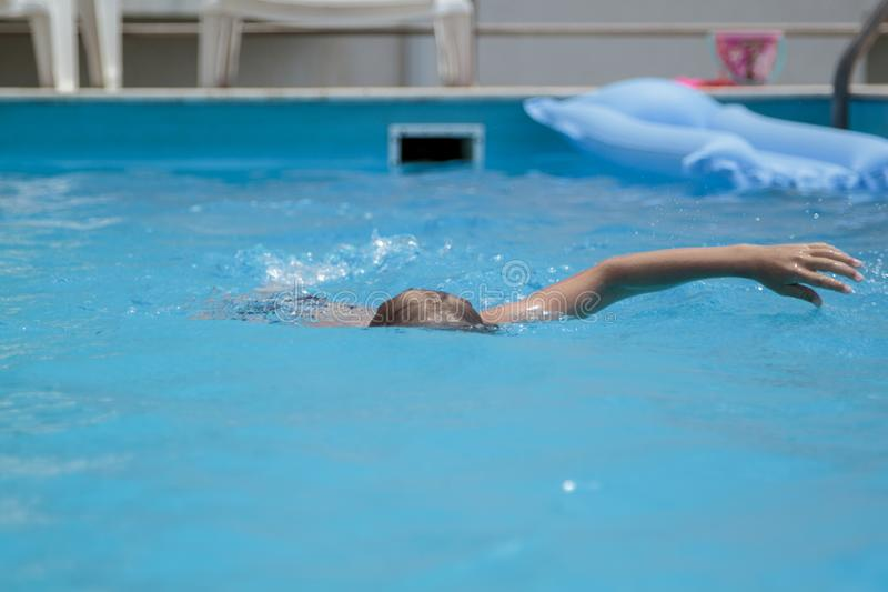 Boy swimming in the pool. Kid, kids, underwater, fun, child, summer, person, vacation, splash, young, smile, blue, dive, swimmer, happy, diving, white, play stock photos