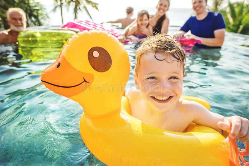 Boy swimming in a pool with family stock photography