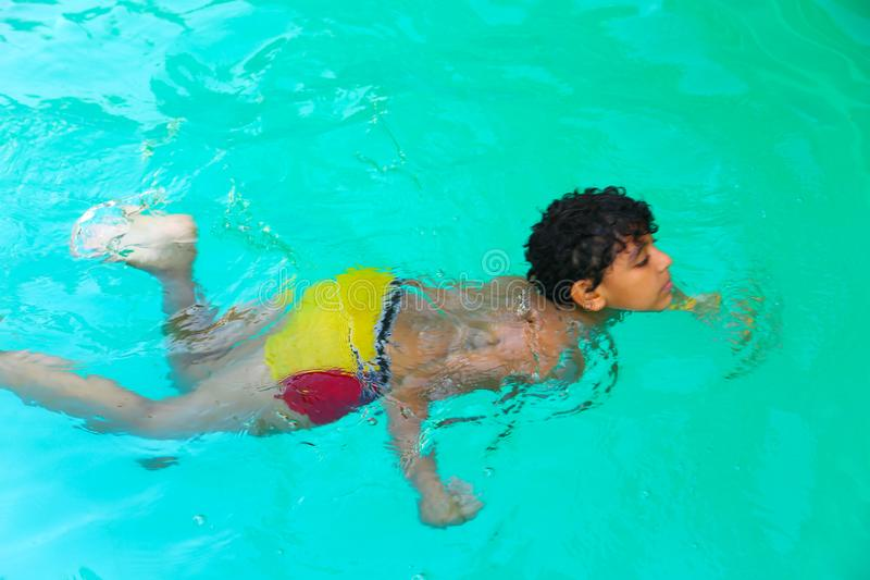 Boy swimming at pool. Happy little boy swimming at pool with diving mask stock photos