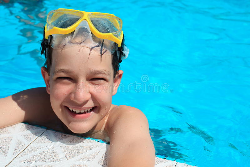 Boy in swimming pool. Happy, smiling boy with goggles in water at the edge of a swimming pool stock image