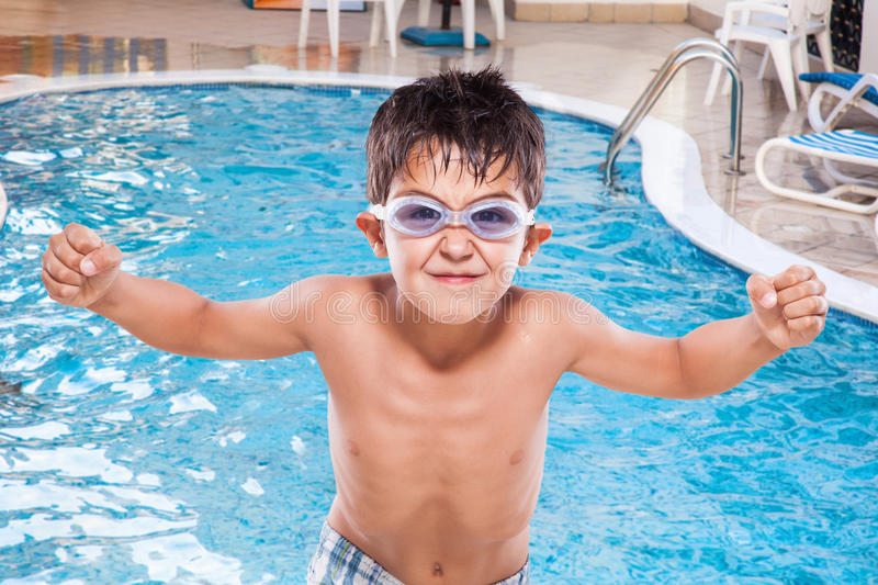 Boy at the swimming pool. A young boy at the swimming pool with his diving goggles stock image