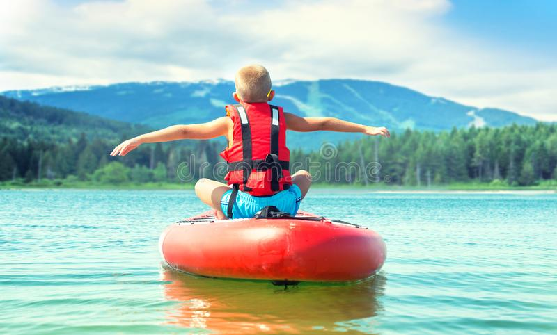 Boy swimming on stand up paddle board.Water sports , active lifestyle. stock photo