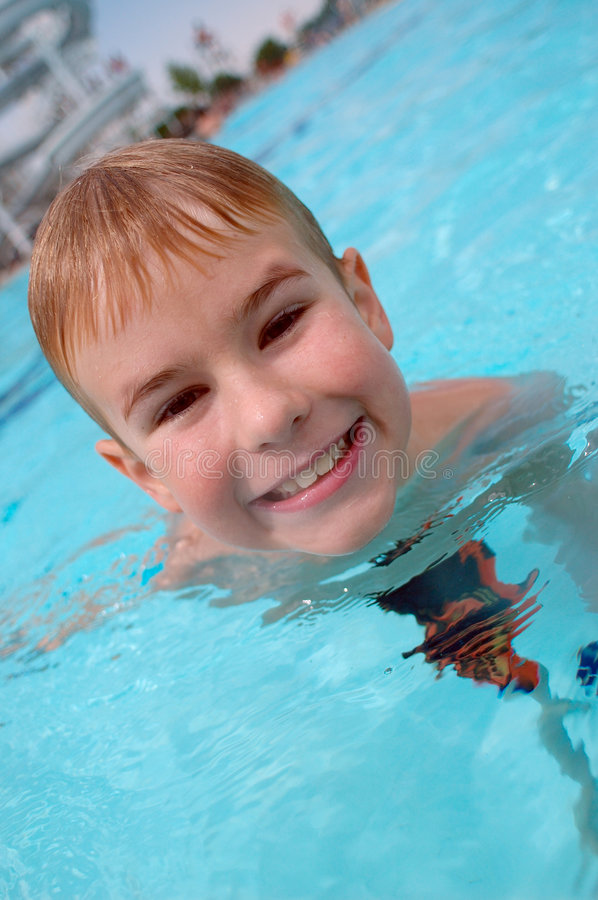 Boy swimming in swimming pool. Happy boy swimming in swimming pool, close shot stock photography