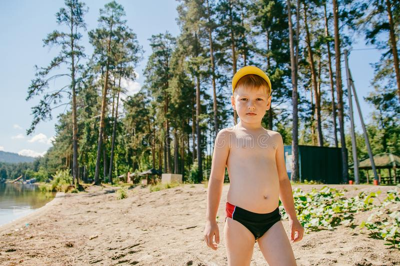 A boy in swimming trunks stands on the sandy shore stock images