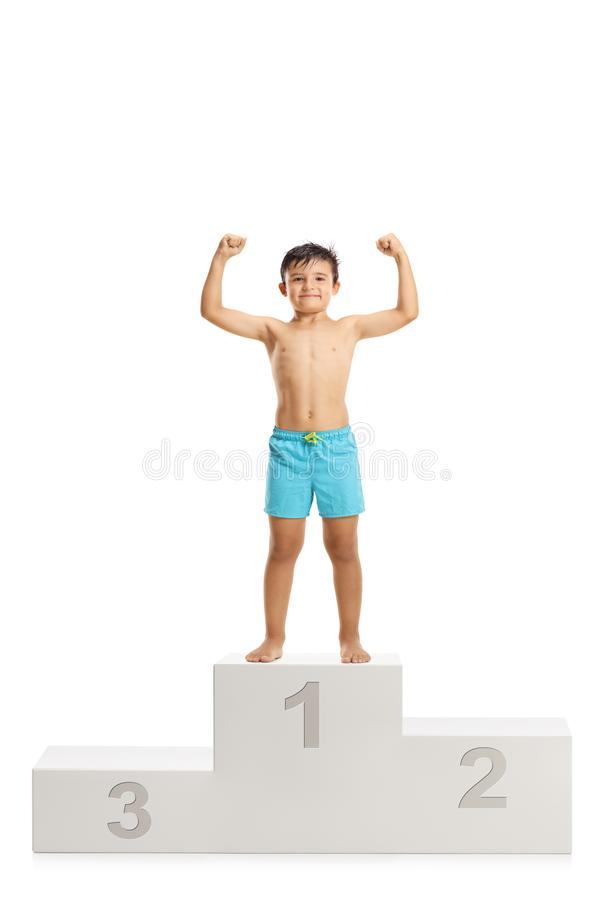 Boy in swimwear standing on a winner`s podium and showing muscle. S isolated on white background stock photography