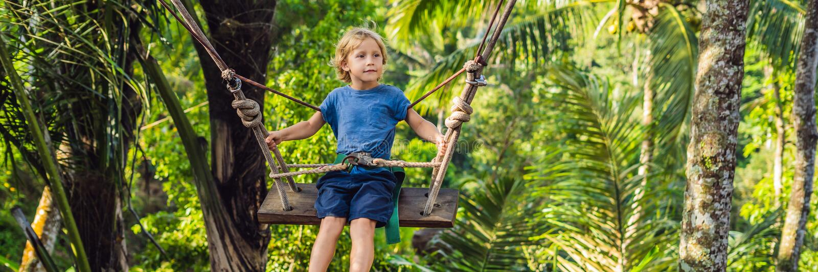 A boy on a swing over the jungle, Bali BANNER, long format. A boy on a swing over the jungle, Bali. BANNER, long format stock images