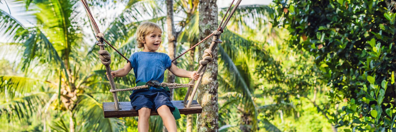 A boy on a swing over the jungle, Bali BANNER, long format. A boy on a swing over the jungle, Bali. BANNER, long format stock photo