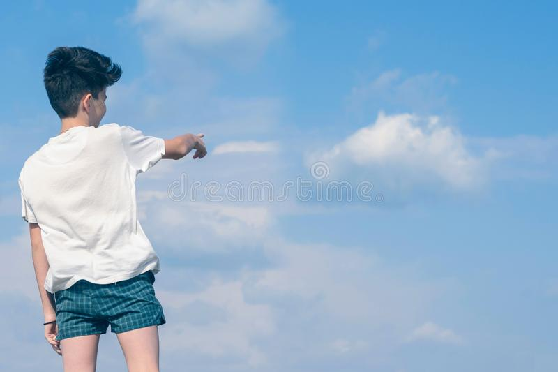 Boy in the T-shirt and shorts shows his finger on the cloudy blue sky and landing plane. Summer and travel concept. stock photo