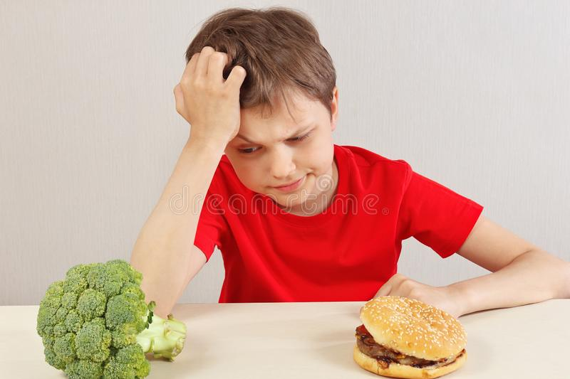 Boy at the table chooses between hamburger and fresh broccoli on white background stock images