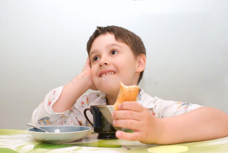 Boy at table eating stock photos