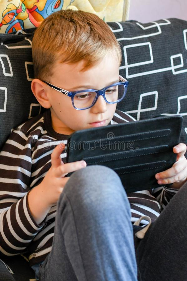 Boy with tablet. Cute little boy with reading glasses for a correction of the vision playing on tablet stock photo