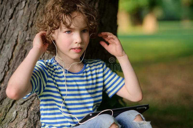 Boy with the tablet listens to music. The boy with the tablet listens to music. The blue-eyed curly boy in earphones has leaned against a trunk of an old tree stock photos