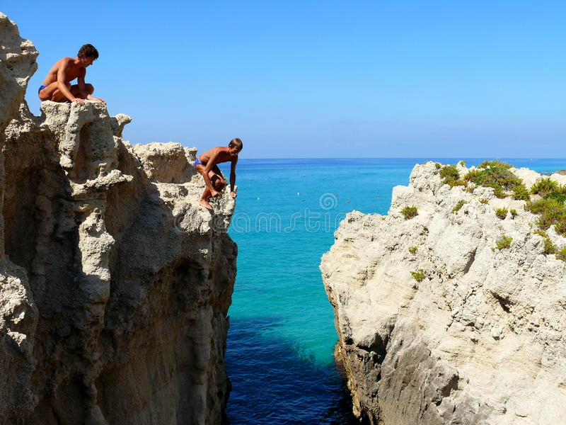 Boy takes courage to jump. Two boys jumping from cliffs to sea royalty free stock photo