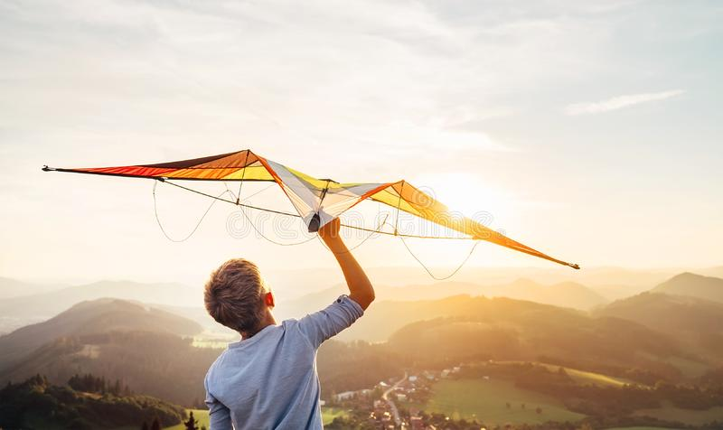 Boy takes a kite over his head. Dreams about flying royalty free stock images