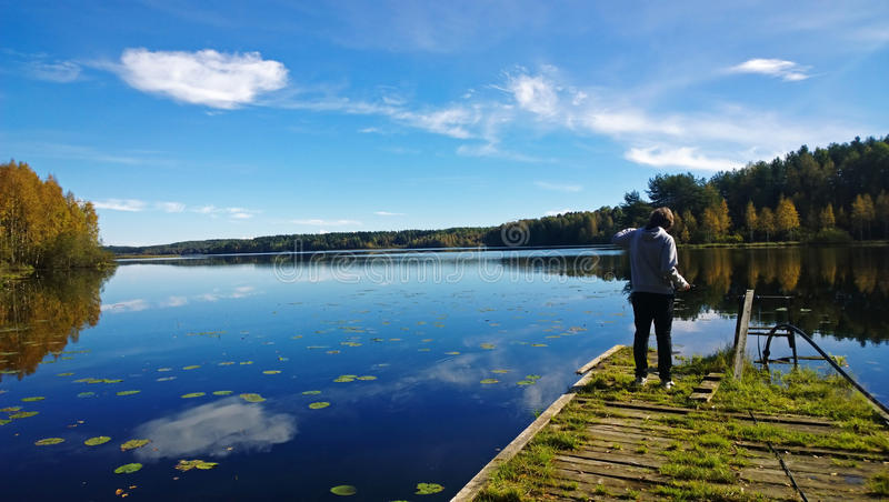 The boy takes a picture of a beautiful lake in autumn day. The view from the back stock photo