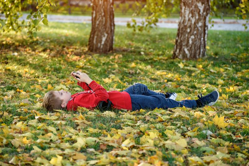 Boy takes pictures while lying on his back. Lawn with autumn foliage. Sunny day stock photo