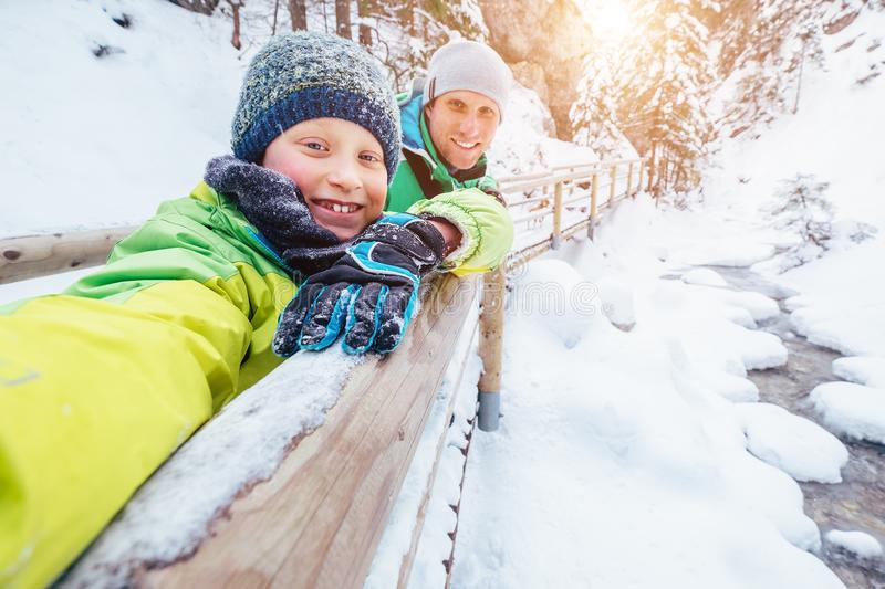 Boy takes self photo with his father on winter walk in mountain royalty free stock photo