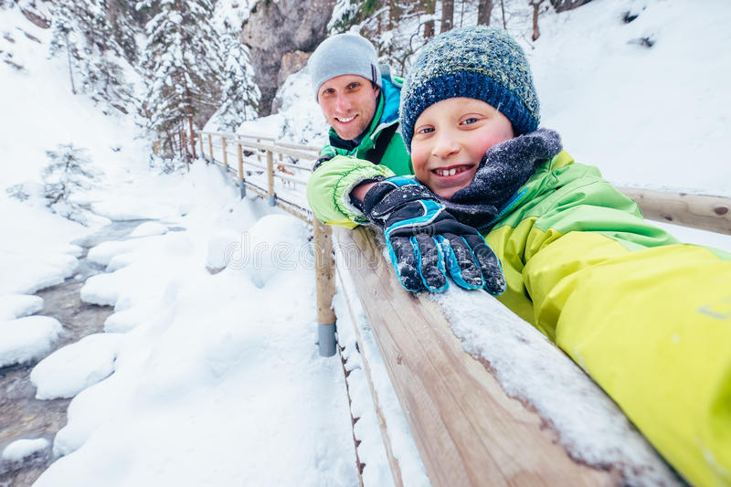 Boy takes self photo with his father on winter walk in mountain stock photography