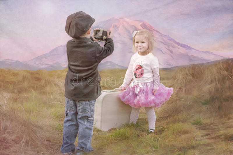 Boy taking girl's picture stock image