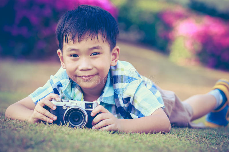 Boy taking photo by camera, exploring nature at park. Active lifestyle, curiosity, pursuing a hobby concept. Vintage. royalty free stock photos