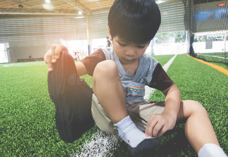 Boy taking shoes off ready for soccer training ground stock photography