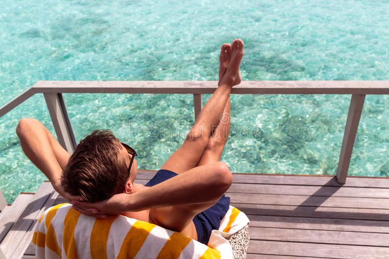Young man in swimsuit relaxing on a terrace and enjoying freedom in a tropical destination. Boy taking a sunbath in the maldives. holiday in paradise concept stock images