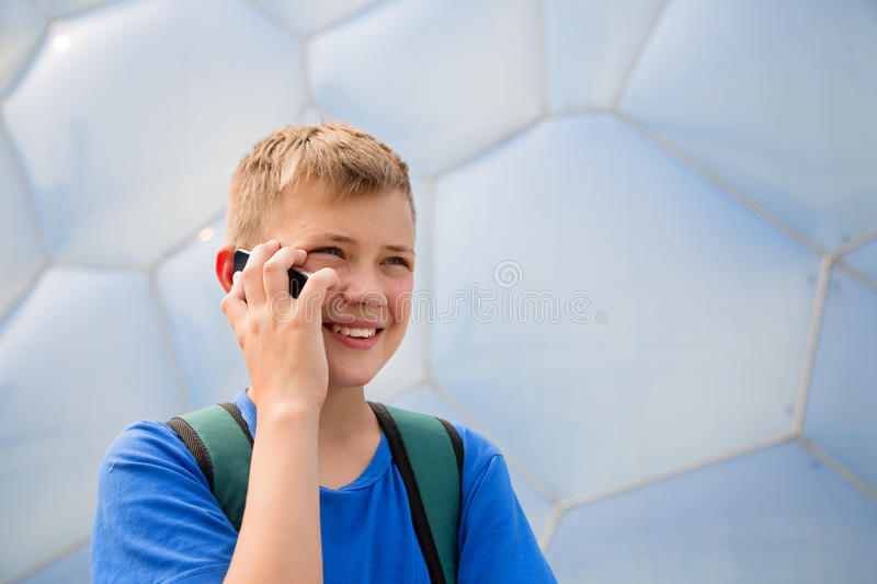 Boy talking on cell phone in the Olympic Park, Beijing. Boy with backpack talking on mobile phone in the Olympic Park in Beijing royalty free stock images