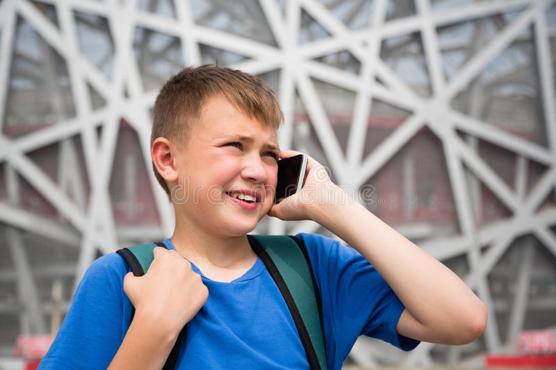 Boy talking on cell phone in the Olympic Park in Beijing. Boy backpacker talking on cell phone in the Olympic Park in Beijing stock image