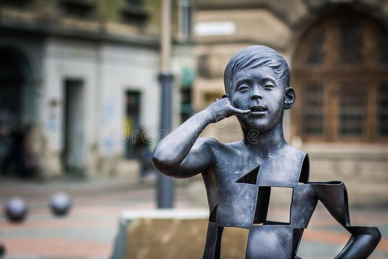 Boy talking on the mobile phone modern art sculpture in Liberty Square of Timisoara stock photo