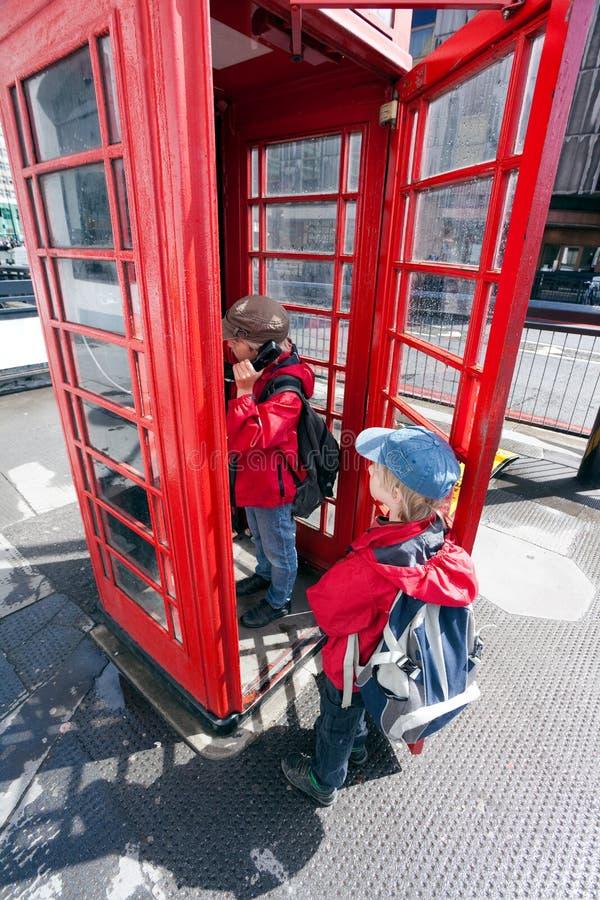 Boy talking in pay phone box royalty free stock photos